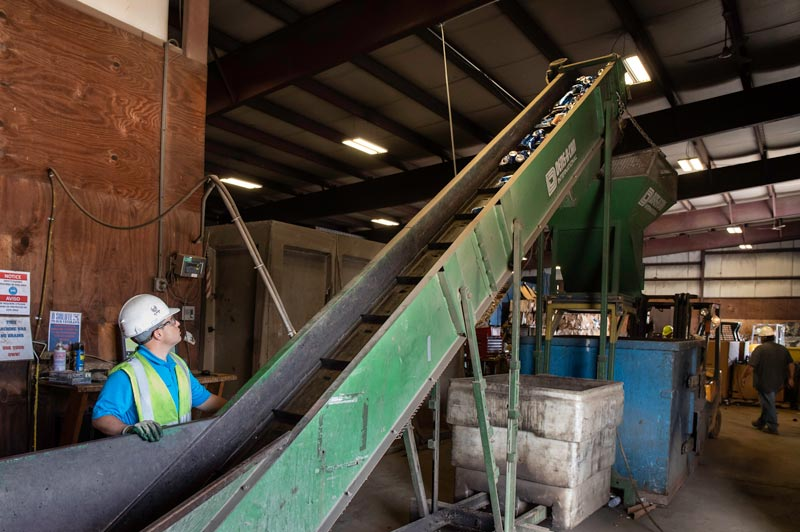 Aluminum cans travel along a conveyor to be sorted and weighed.