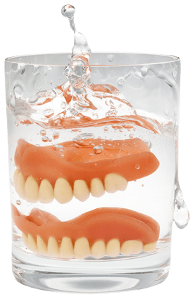 Dentures being dropped into a glass of water
